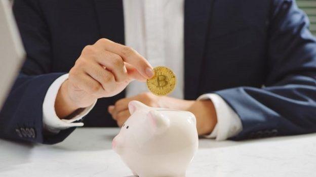 homem guardando moeda de bitcoin no cofre de porquinho