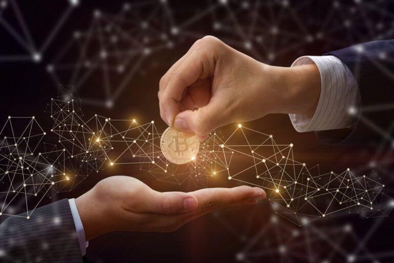 mão passando uma moeda de bitcoin pra outra mao