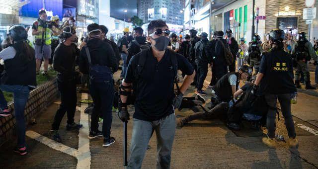 homem com máscara num protesto