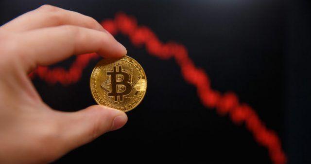 mão segurando uma moeda de bitcoin