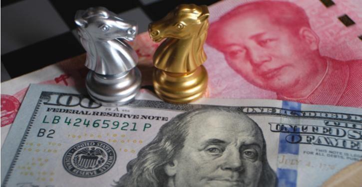 Imagem de notas de dólar americano e yuan chinês com peças de xadrez representando a recente guerra comercial